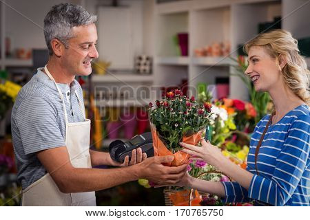 Florist giving bouquet of flower to woman in flower shop