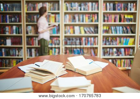 Open books on desk and human by bookshelf on background