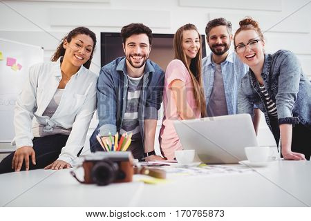 Portrait of cheerful young editors standing at creative office