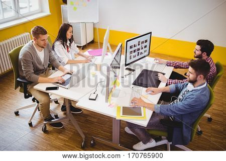 High angle view of young editors working at creative office