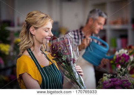 Happy female florist smelling a flower bouquet in flower shop