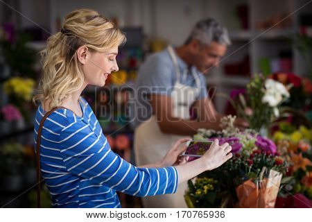 Woman taking photograph of flower bouquet in flower shop