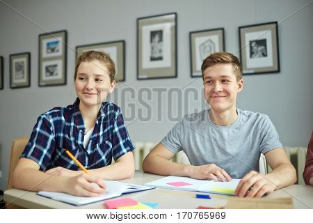 Students making notes while listening to explanation of teacher