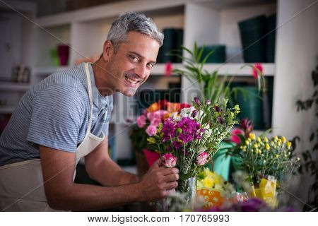 Portrait of happy florist preparing a flower bouquet in flower shop