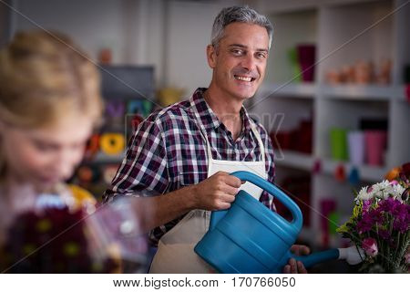 Portrait of male florist watering flowers with watering can in flower shop