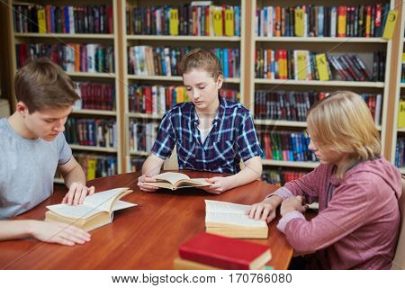 Three students reading books in college library
