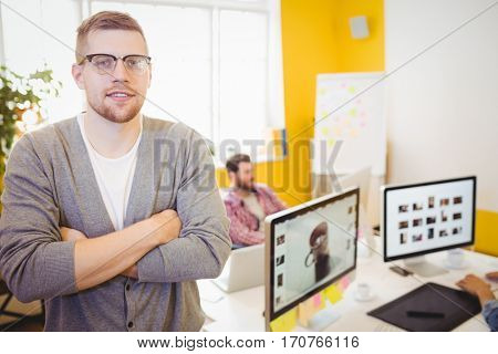 Portrait of confident young male editor with arms crossed at creative office