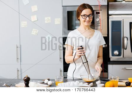 Woman using electric blender for whisking raw eggs