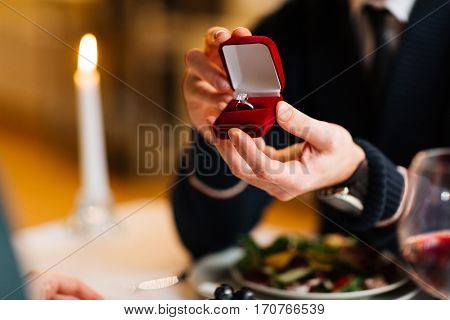 Young man showing his girlfriend red velvet box with engagement ring