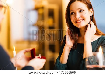 Smiling woman looking at sweetheart while he making proposal to her