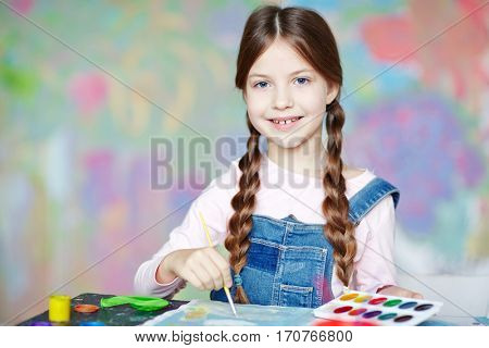 Happy girl with pigtails painting picture