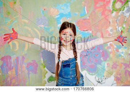 Cheerful schoolkid with outstretched arms and painted palms