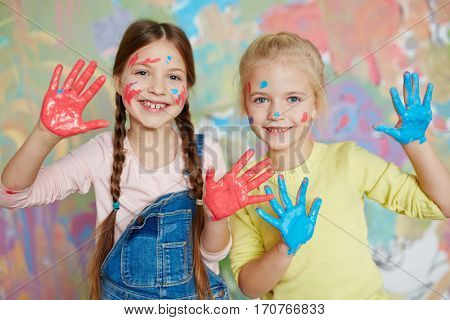 Smiley girls with blue and red palms looking at camera