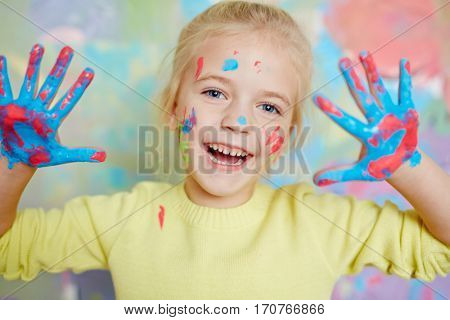 Laughing girl with vibrant colors on her palms and face