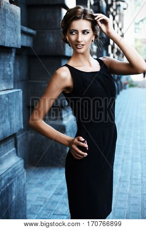 Vogue model wearing black dress posing over urban background. Fashion shot.