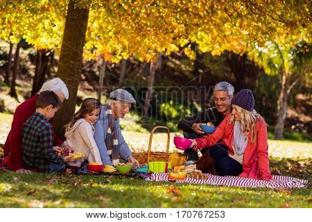 Happy multi-generation family having breakfast at park during autumn