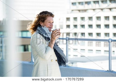 Mature woman drinking coffee by railing in city