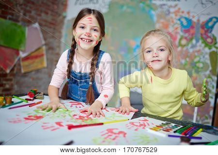 Creative girls making their hand-prints on paper