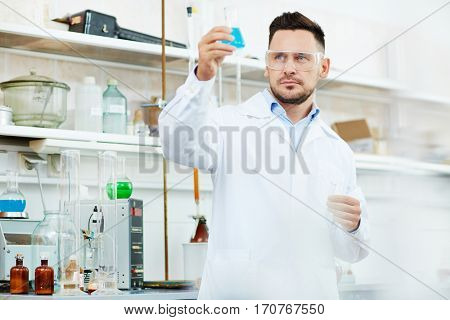 Clinician in whitecoat and protective eyeglasses looking at tube with liquid substance poster