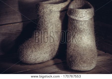 traditional Russian felt boots very warm shoes for cold winter, on old wooden table, light brush,  toning.