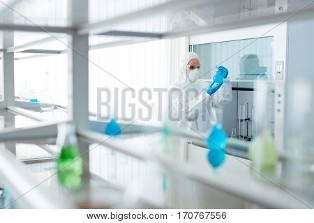 Chemist in overalls and respirator looking at toxic liquid in tube