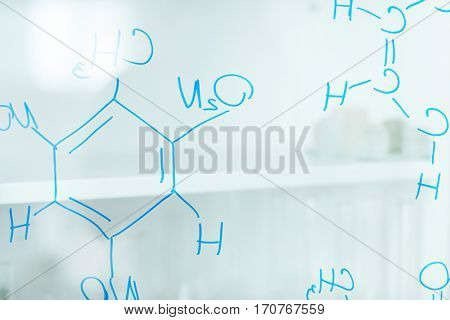 Formula of molecular structure drawn with blue highlighter on transparent board
