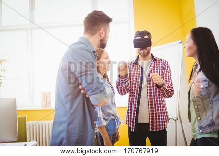 Coworkers looking at businessman wearing virtual reality headset in creative office