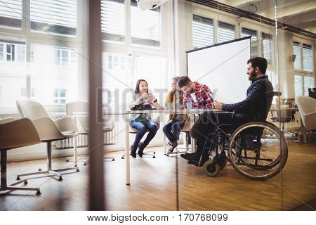 Coworker on wheelchair with photo editors in meeting room at creative office