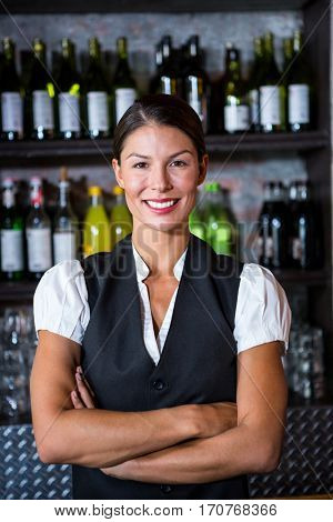 Smiling waitress with arms crossed in a restaurant