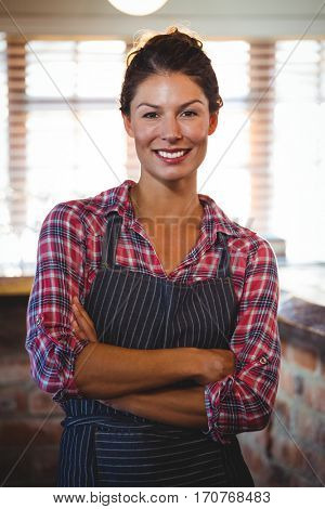 Waitress standing with arms crossed in a cafe