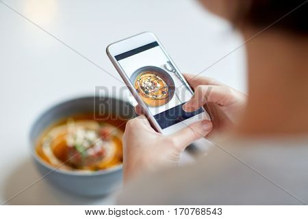 food, new nordic cuisine, technology, eating and people concept - woman with smartphone photographing bowl of vegetable pumpkin-ginger soup with goat cheese and tomato salad with yogurt at restaurant