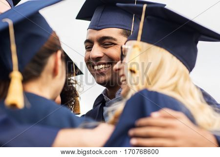 education, graduation and people concept - group of happy international students in mortar boards and bachelor gowns hugging outdoors