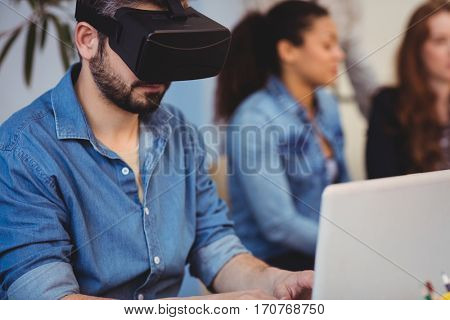 Businessman wearing virtual reality headset against female coworkers in creative office