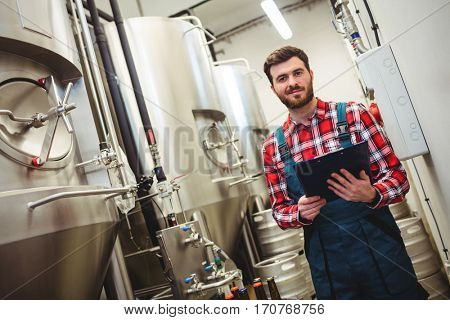 Portrait of young manufacturer holding writing pad in brewery