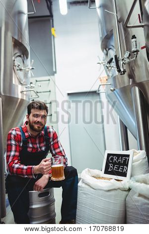 Portrait of manufacturer with beer glass while sitting by storage tank at brewery