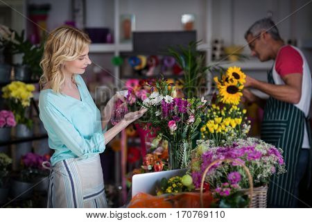 Smiling florist spraying water on flowers in flower shop