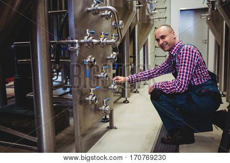Portrait of manufacturer adjusting pressure gauge in brewery