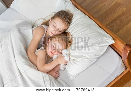 two cute little sisters sleeping in white bed