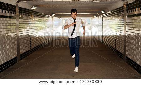 Young businessman running through underpass.