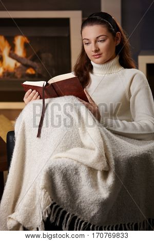 Portrait of young woman sitting in living room at fireplace, covered in blanket, reading book, looking down.