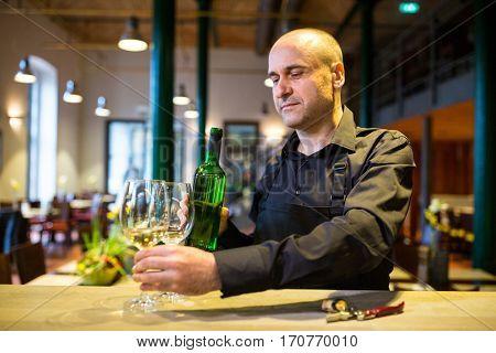 Waiter holding glasses and a bottle of white wine in restaurant