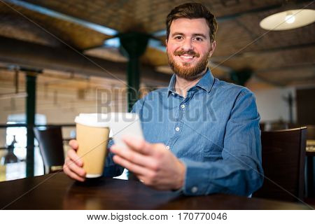 Portrait of man holding disposable coffee cup and mobile phone in restaurant