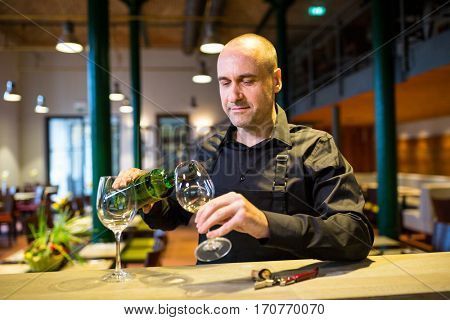 Waiter pouring white wine into glass in restaurant