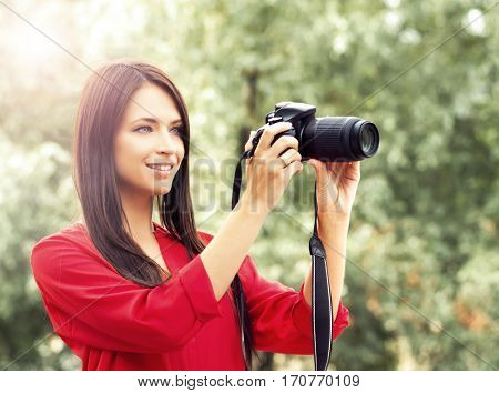 Young and beautiful girl with a photo camera. Amateur female photographer with new dslr in the park.