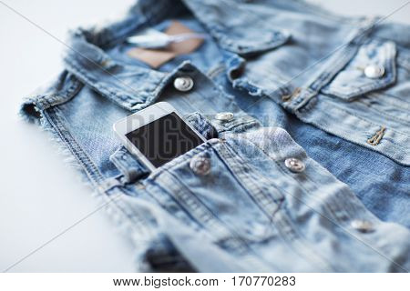 technology and communication concept - smartphone in pocket of denim jacket or waistcoat