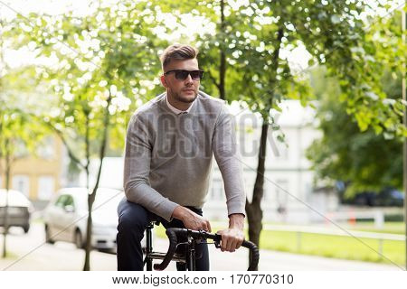 lifestyle, transport and people concept - young man in sunglasses riding bicycle on city street