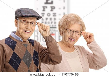 Seniors smiling in front of an eye chart isolated on white background