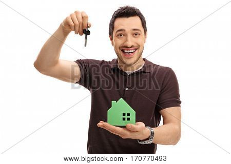 Joyful guy holding a key and a model house isolated on white background