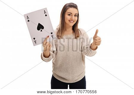 Joyful girl holding an ace of spades card and giving a thumb up isolated on white background