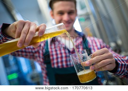 Close-up of brewer pouring beer in glass at brewery factory